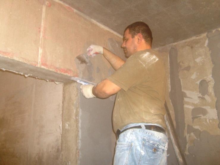 Мастер шпаклюет стену